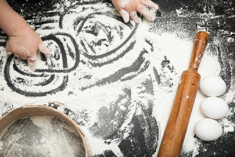Ð¡hild`s hand is playing with flour, ingredients for baking stock image