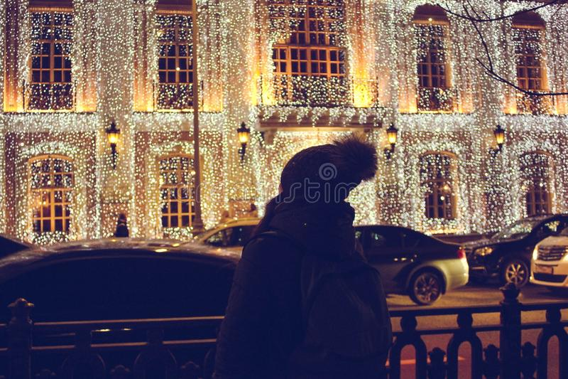 Girl standing with her back to the camera and looking at the christmas lights and enjoys the holiday atmosphere royalty free stock images