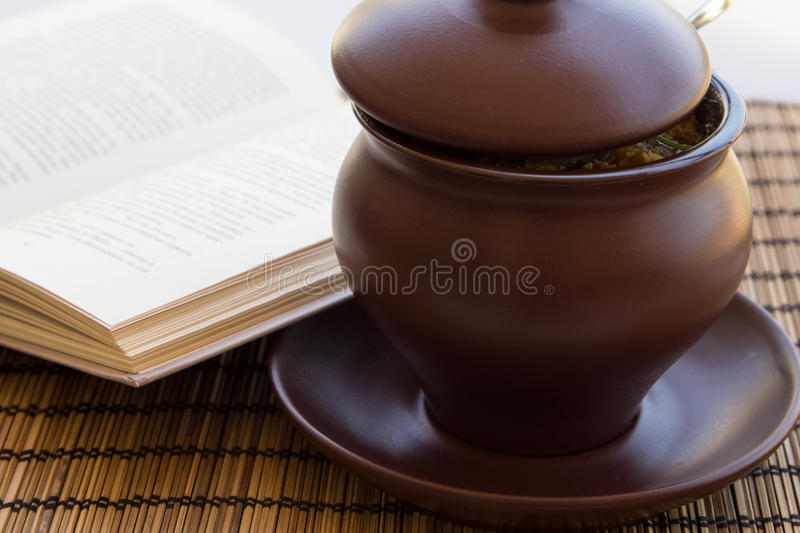 Ð¡lay pot on a napkin with book. Roast with meat, potatoes in a clay pot on a napkin with book stock image