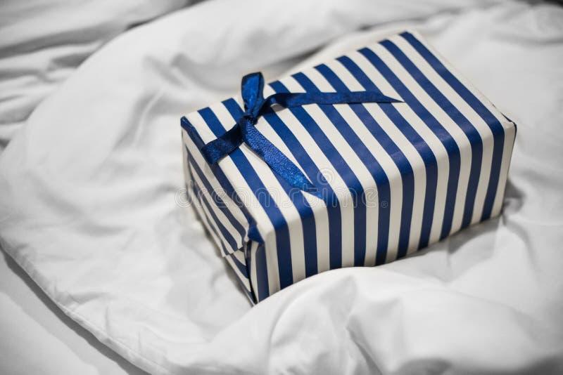 Сlose επάνω του μπλε ριγωτού δώρου για ένα άτομο σε ένα άσπρο κρεβάτι Έκπληξη πρωινού στοκ φωτογραφίες