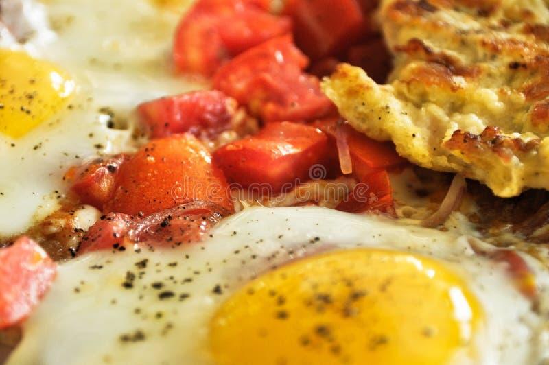 ?lose su di tuorlo dalle uova fritte e dai pomodori affettati con la cipolla per la prima colazione senza piatto immagini stock