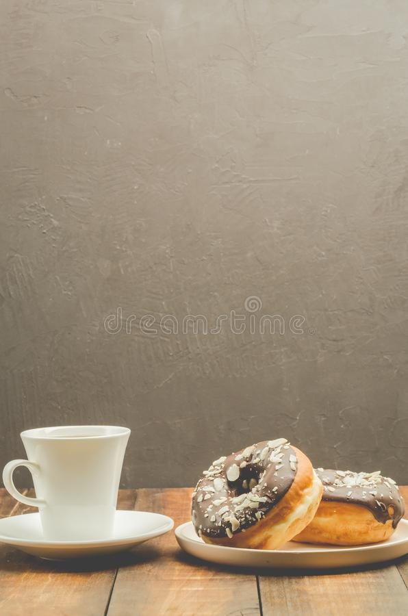 Ð¡offee break. White cup with black coffee and donat in chocolate glaze. Dark background with copy space royalty free stock images