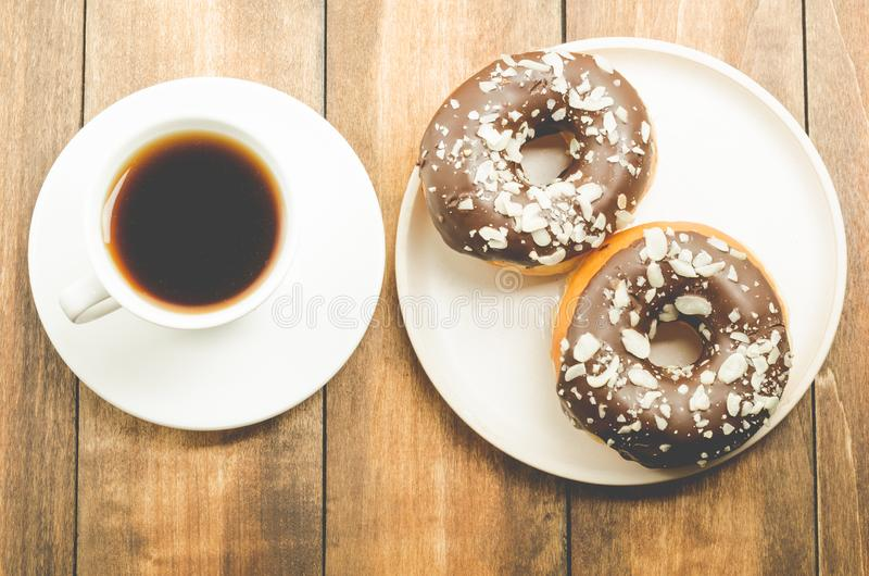 Ð¡offee break. White cup with black coffee and donat in chocolate glaze. Wooden background, top view royalty free stock photos