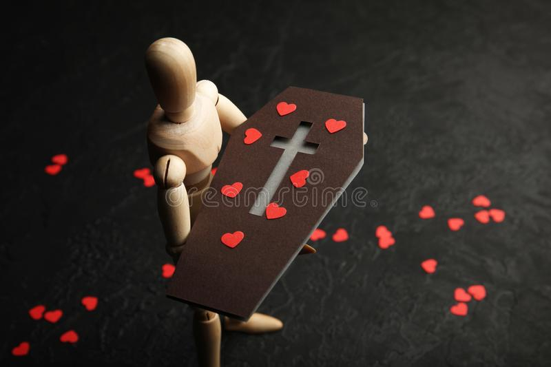 Ð¡offin in hands of wooden man. Sadness and loss of loved one. Death.  royalty free stock images