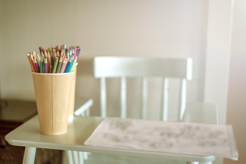 Сolored blyertspennor är på den höga stolen arkivfoton