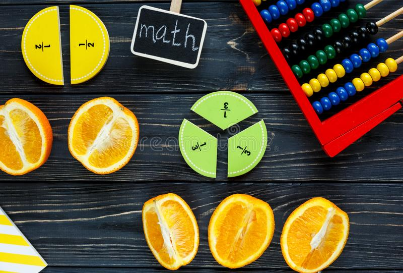 Ð¡olorful math fractions and oranges as a sample on dark wooden background or table. Interesting creative funny math for kids stock image