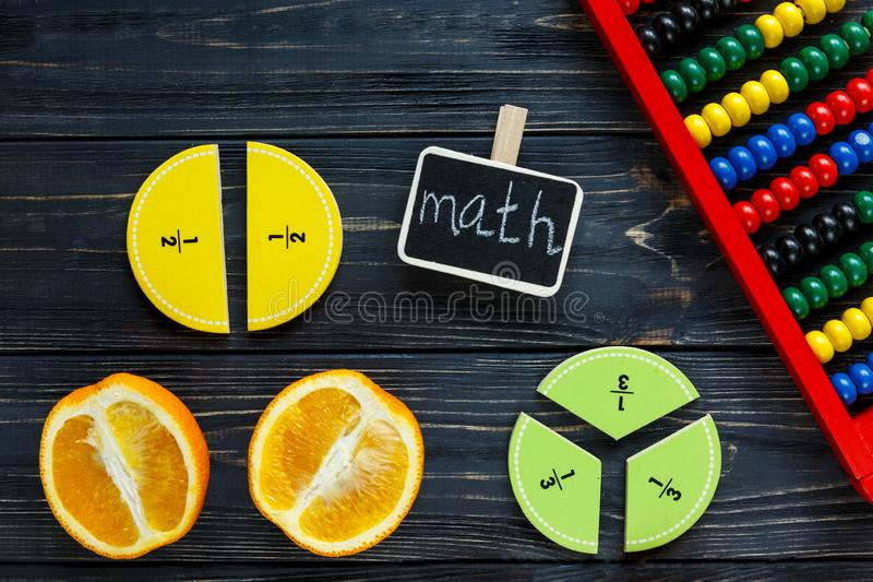 Ð¡olorful math fractions and oranges as a sample on dark wooden background or table. Interesting creative funny math for kids royalty free stock photos