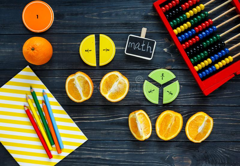 Ð¡olorful math fractions and oranges as a sample on dark wooden background or table. Interesting creative funny math for kids royalty free stock image