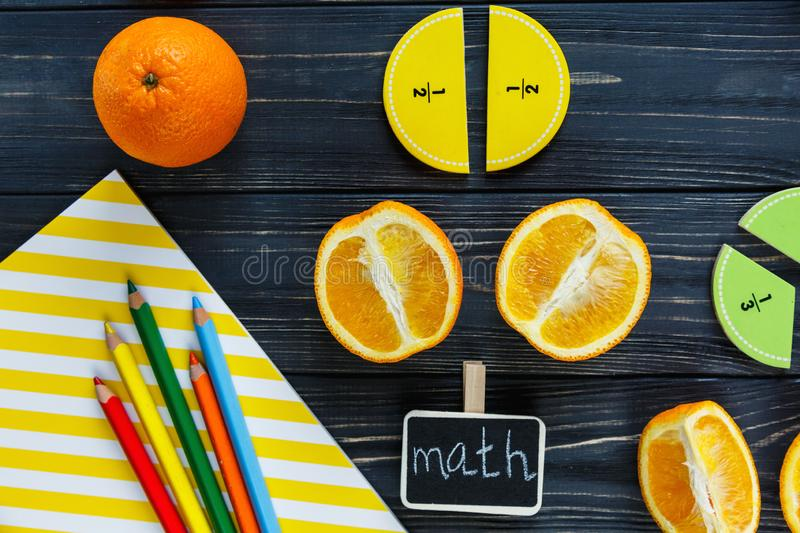 Ð¡olorful math fractions and oranges as a sample on dark wooden background or table. Interesting creative funny math for kids royalty free stock photography