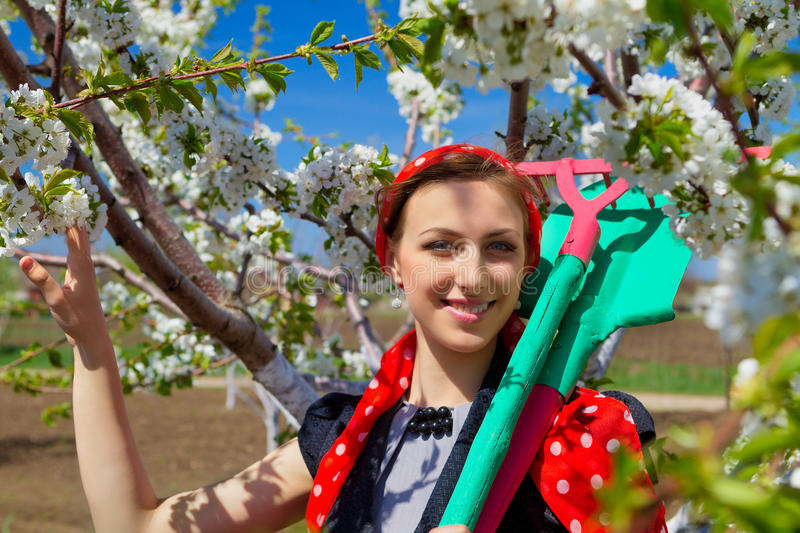 Ð¡ommunity work day. Portrait of young female with rakes on garden royalty free stock photo
