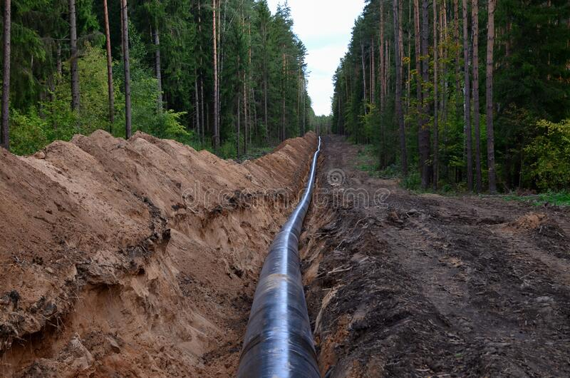 Ð¡onstructing pipelines that transport oil, natural gas, petroleum products and industrial gases. A dug trench in the ground for. The installation of royalty free stock photo