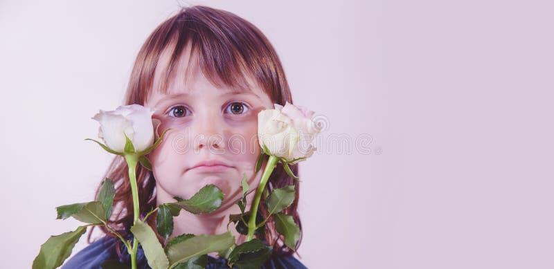 ?ute e menina bonita da criança com rosas Express?o facial engra?ada fotografia de stock royalty free