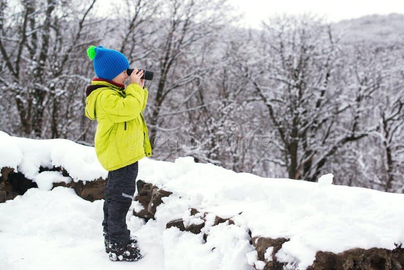 ?ute-Kindernaturforscher im Fernglasforscher des Winterwaldkleinen Jungen an der Winternatur Schneemann gebildet vom wei?en tropi lizenzfreies stockfoto