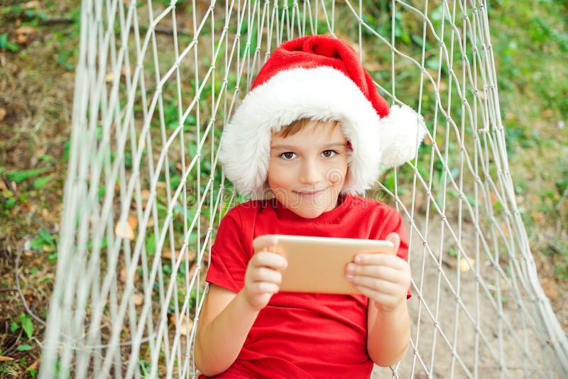 Сute little boy watching christmas cartoons on family vacations. Happy kid in Santa hat lying in hammock. Family travelling to. Tropical countries. Happy child stock images