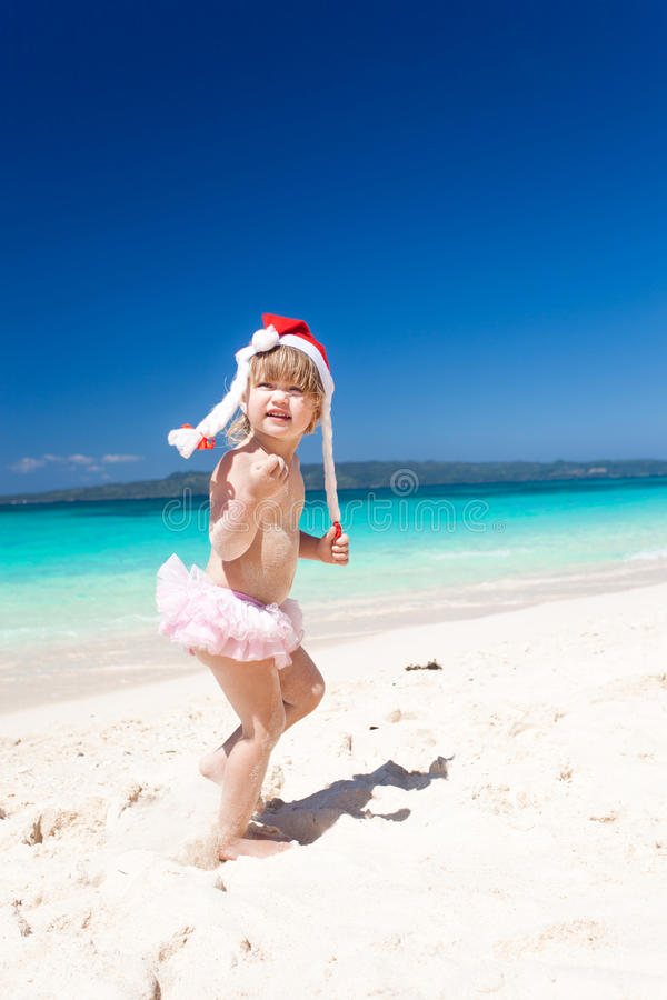 ?utemeisje in Kerstmanhoed op strand royalty-vrije stock afbeelding