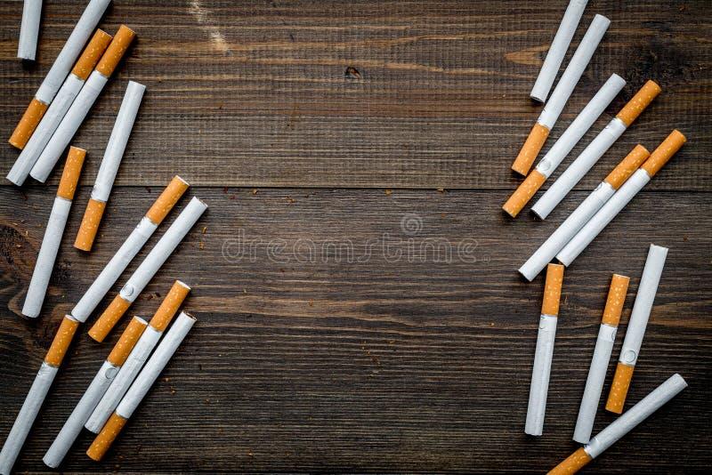 табак Разбросанные сигареты на темном деревянном космосе экземпляра взгляд сверху предпосылки стоковое изображение