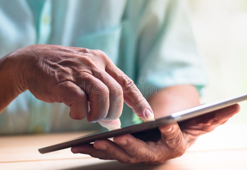 Таблетка владением старика с левым экраном руки и касания с правым указательным пальцем стоковая фотография rf
