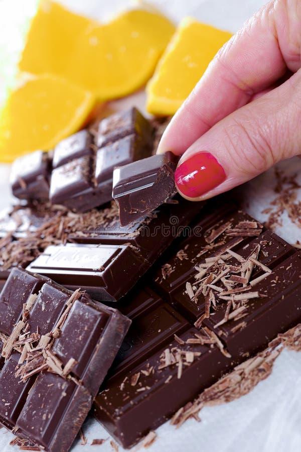 Таблетка и части темного шоколада с пальцем женщины стоковые изображения rf