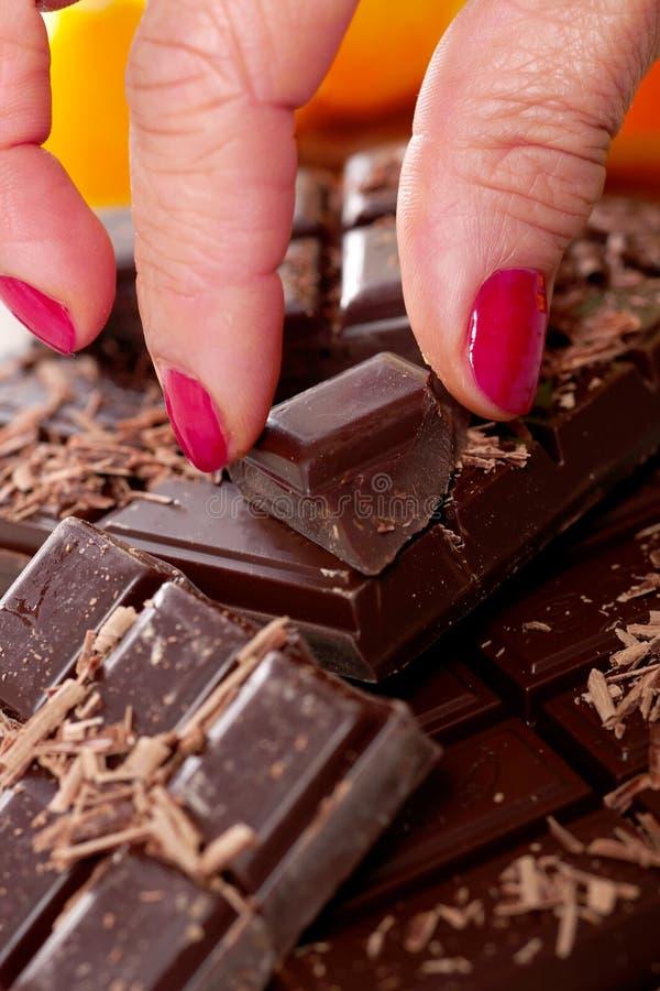 Таблетка и части темного шоколада с пальцем женщины стоковое изображение rf