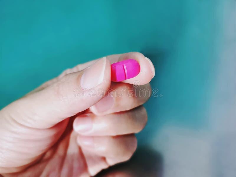 Таблетка лекарства пинка удерживания руки с выборочным фокусом стоковые фотографии rf