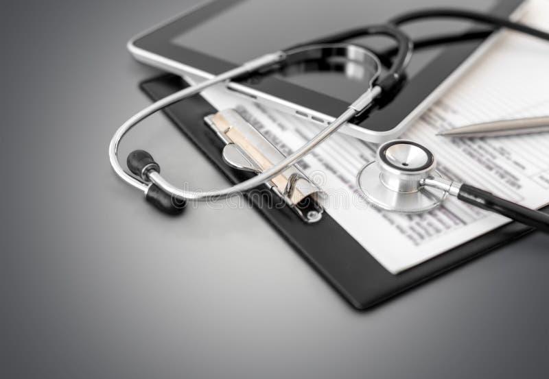 Таблетка цифров с стетоскопом и обработкой документов стоковая фотография rf