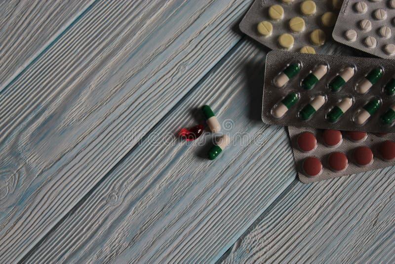 Таблетки, витамины и капсулы на сером деревянном столе стоковое изображение rf