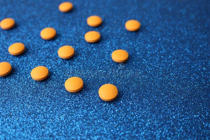 Таблетки небольшого желтого апельсина красивые медицинские pharmaceptic круглые, витамины, лекарства, антибиотики на голубой пред стоковая фотография