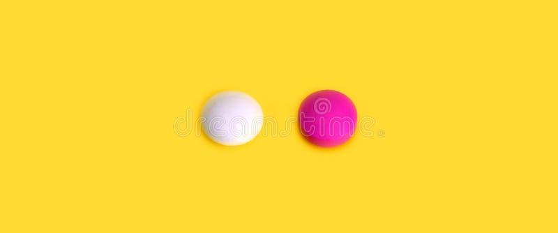 2 таблетки пинк и белое на желтой предпосылке стоковые фотографии rf