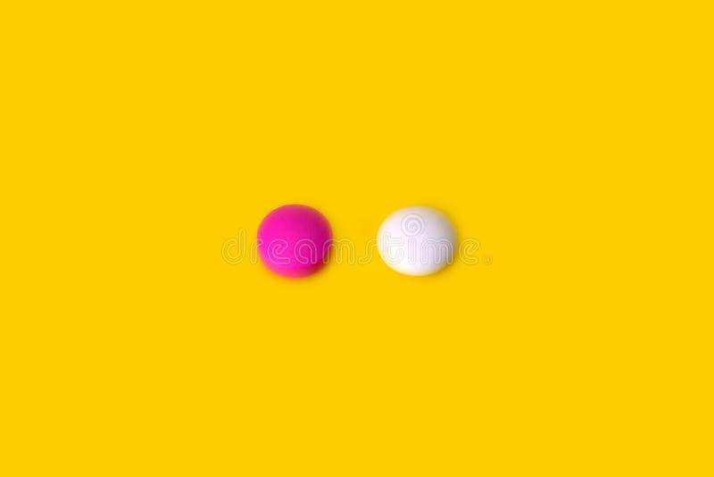 2 таблетки пинк и белое на желтой предпосылке стоковое изображение