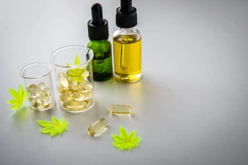 Таблетки, планшеты, капсулы и масло пеньки марихуаны конопли и CBD в beaker масштаба лаборатории стеклянном как обезболивающее и  стоковые изображения rf