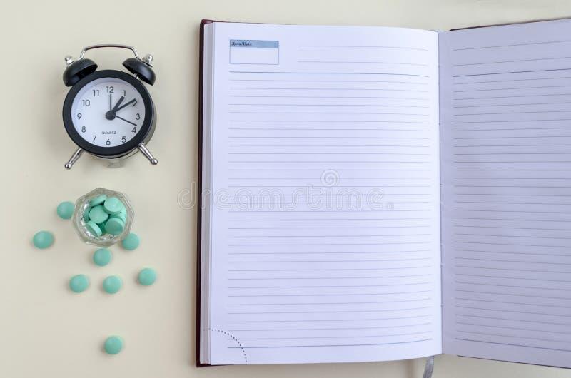 Таблетки политы из стеклянной чашки, таблеток разбросали, таблетки взятия в срок, пишут в календаре и дневнике r стоковое изображение rf