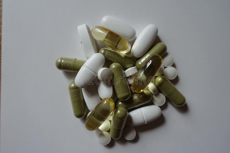 Таблетки, caplets, softgel и капсулы целлюлозы в куче стоковая фотография