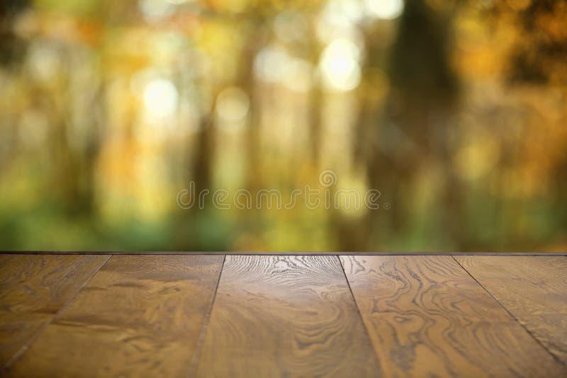 Таблица деревянной доски осени пустая перед запачканной предпосылкой Пустой деревянный стол перед абстрактной запачканной предпос стоковое изображение