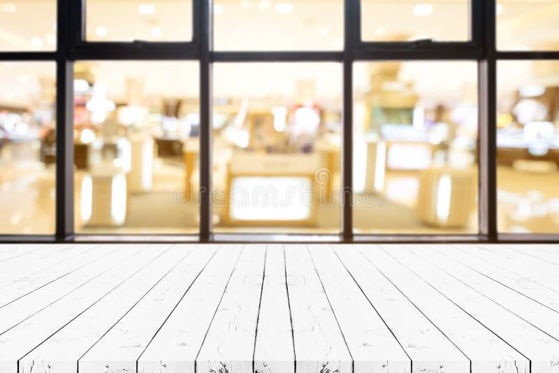 Таблица деревянной доски перспективы белая пустая на верхней части над запачканной предпосылкой универмага, может быть используем стоковая фотография rf