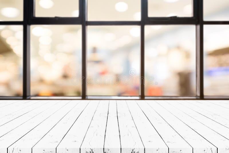 Таблица деревянной доски перспективы белая пустая на верхней части над запачканной предпосылкой универмага, может быть используем стоковые изображения