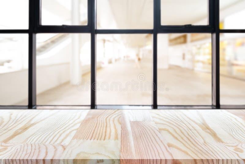 Таблица деревянной доски перспективы пустая на верхней части над запачканной предпосылкой кофейни, может быть используемое насмеш стоковые фото