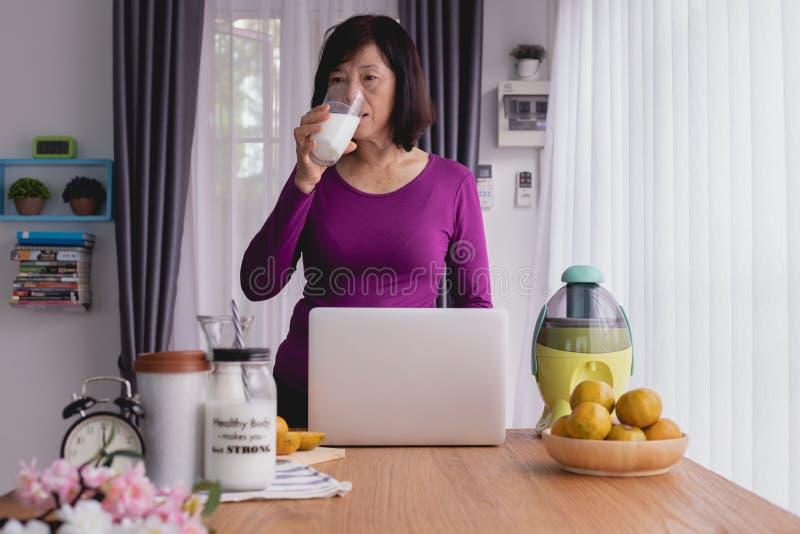 Таблица завтрака с азиатской пожилой женщиной выпить некоторое молоко в живущей комнате дома стоковые изображения