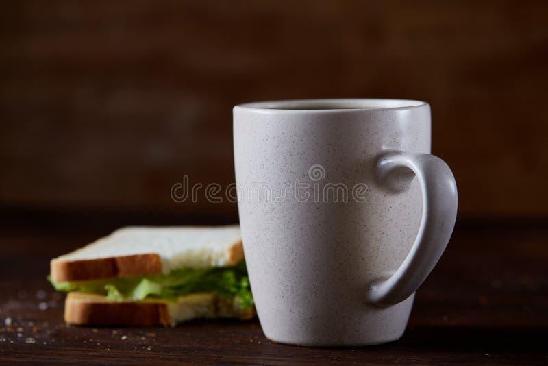 Таблица завтрака с сандвичем и черным кофе на деревенской деревянной предпосылке, конце-вверх, селективном фокусе стоковая фотография rf