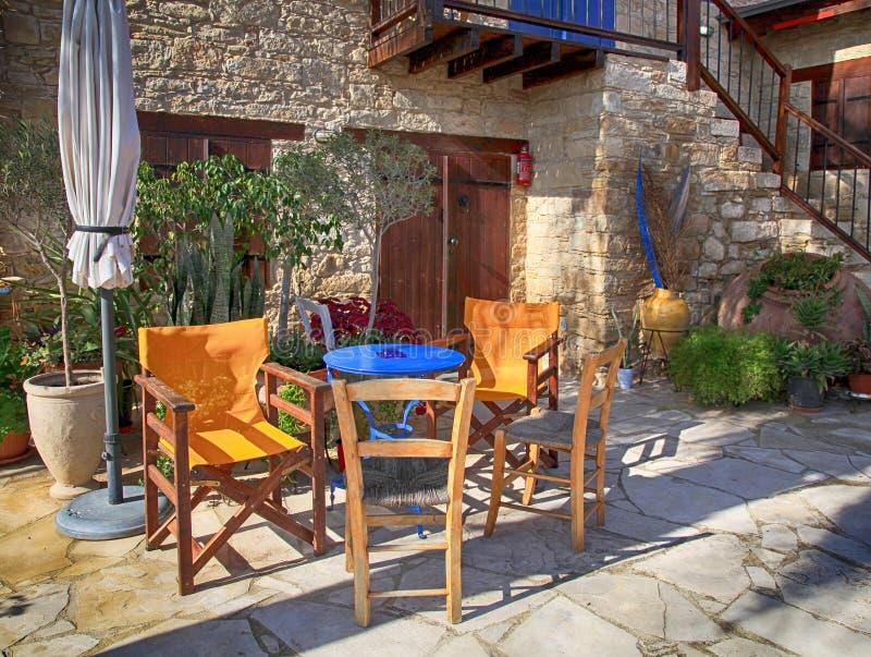 Таблица и внешние стулья на террасе с цветочными горшками стоковое изображение