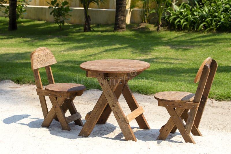 Таблица и деревянные стулья в тропическом саде рядом с морем на песке приставают к берегу, Таиланд конец вверх стоковое фото