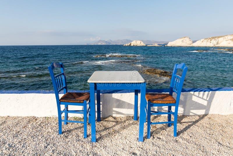 Таблица и стулья стоя на побережье Эгейского моря в греческом острове Milos стоковое изображение rf