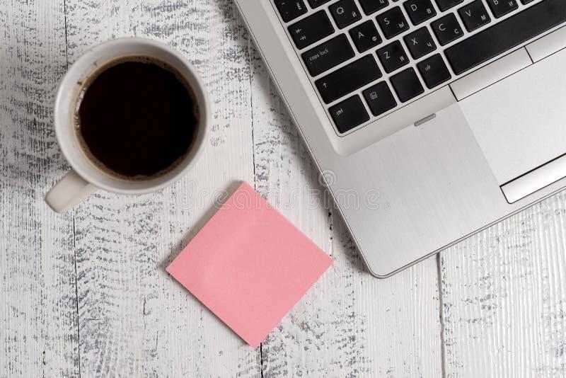 Таблица кофейной чашки примечаний ультрамодного металлического ноутбука липкая лежа деревянная деревенская винтажная Рабочий стол стоковое фото
