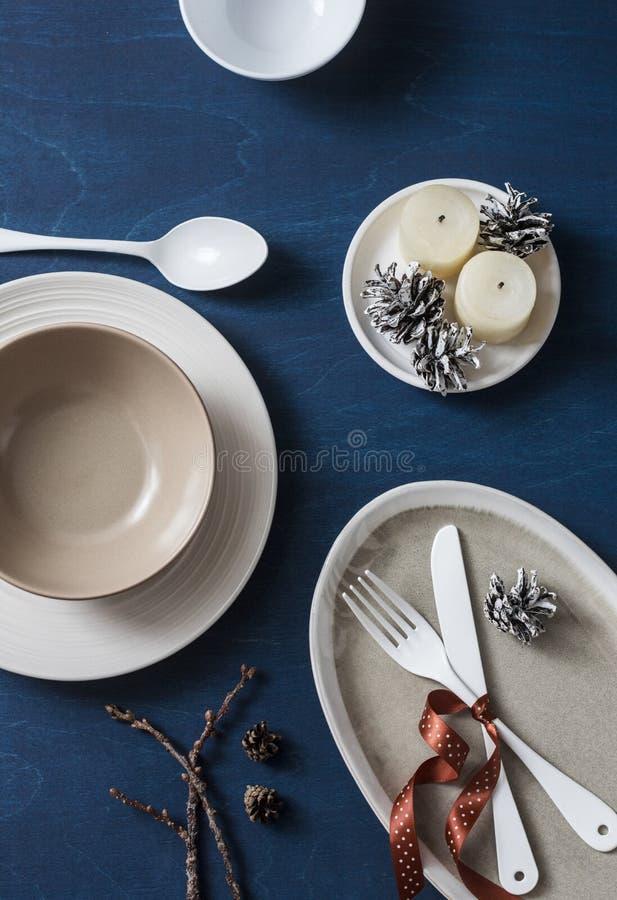 Таблица обеда рождества служат едой, который Пустые плиты, шары, вилка, нож, ложка, украшения рождества, конусы и свечи на голубо стоковые изображения rf