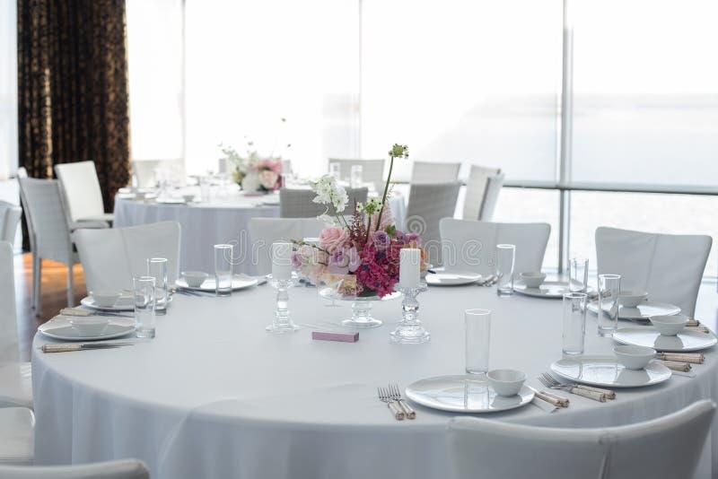 Таблица ресторана события, который белая служат и украшаемые с чувствительными свежими цветками стоковые фотографии rf