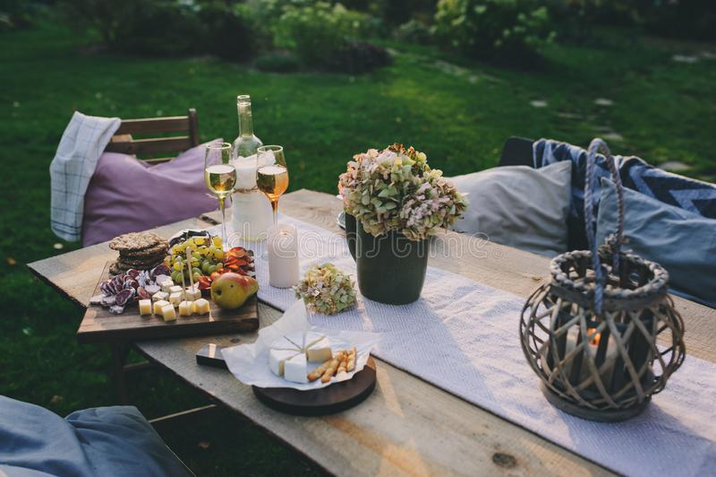 Таблица сада лета украшенная с цветками и свечами, партией вечера с вином стоковое фото rf
