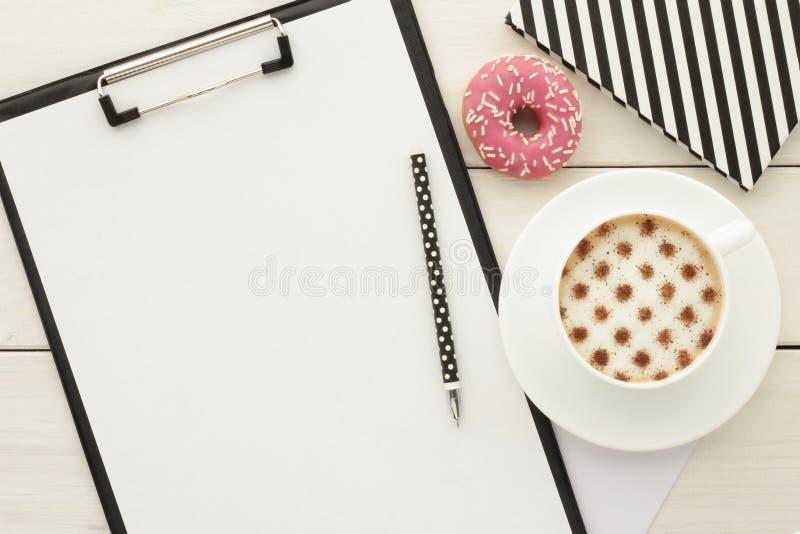 Таблица стола офиса с доской сзажимом для бумаги и чашкой кофе стоковые изображения