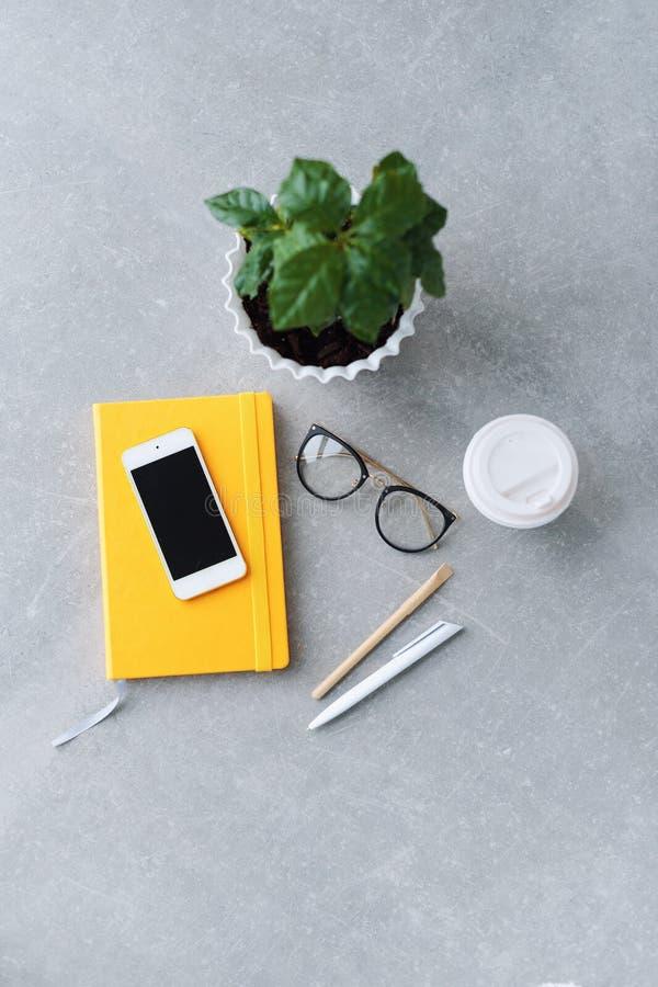 Таблица стола офиса с плановиком тетради, умным телефоном, стеклами, деревом кофе и кофейной чашкой Взгляд сверху с космосом экзе стоковые фото