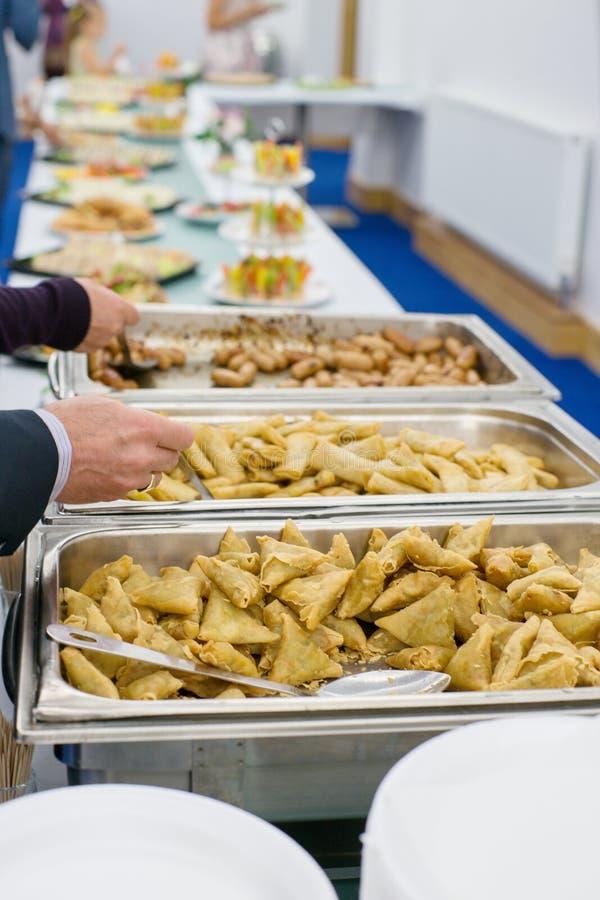 Таблица с банкетом и рукой еды с ложкой стоковое фото