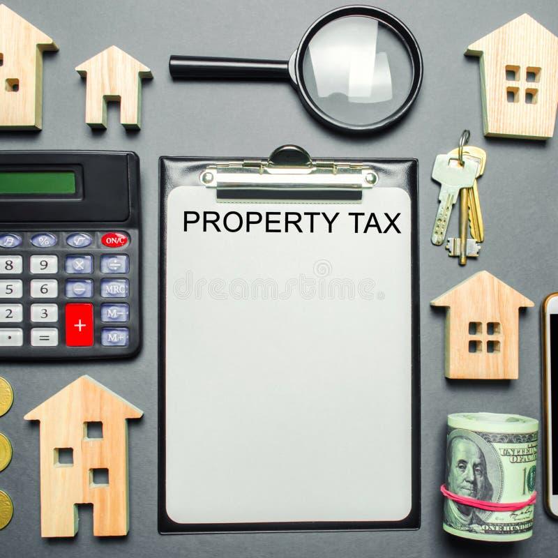 Таблица с деревянными домами, калькулятор, монетки, лупа с налогом на собственность слова Налоги на собственность Вычисление инте стоковая фотография