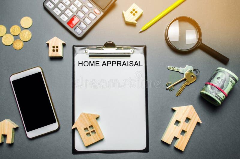 Таблица с деревянными домами, калькулятор, монетки, лупа с оценкой слова домашней Оценка имущества контракта по-настоящему стоковая фотография rf